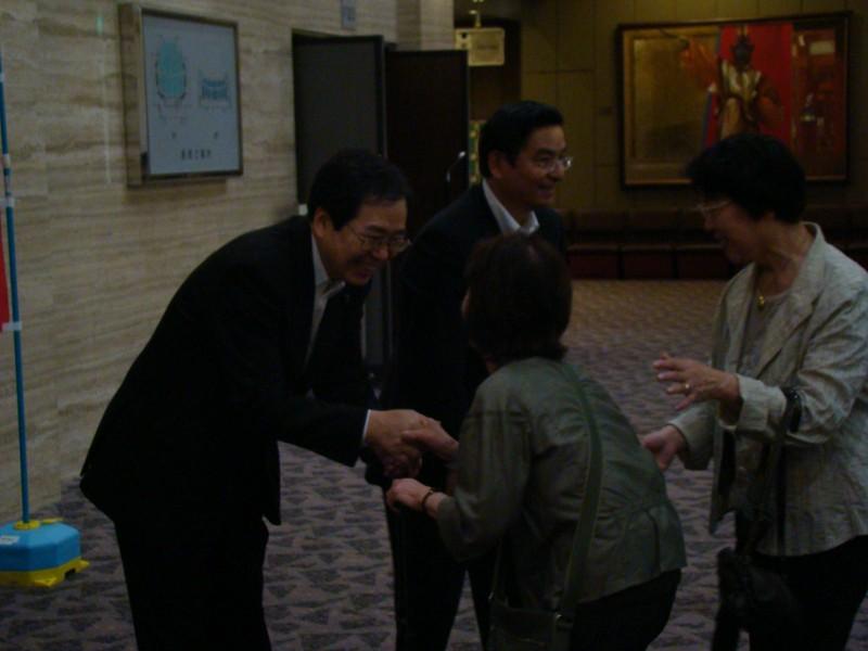 参加者を出迎える 斉藤鉄夫(左)と山本ひろし参院議員