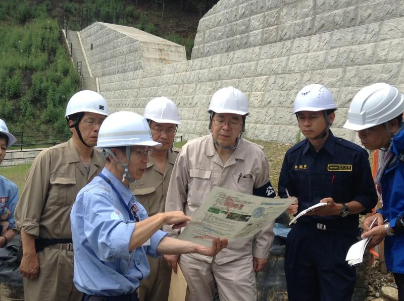砂防堰堤で国交省担当者の説明を受ける 斉藤鉄夫(右から3人目)ら