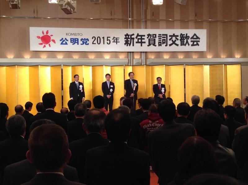 あいさつする 斉藤鉄夫(檀上右から2人目)