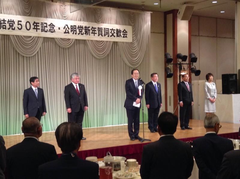 あいさつする 斉藤鉄夫(壇上左から3人目)
