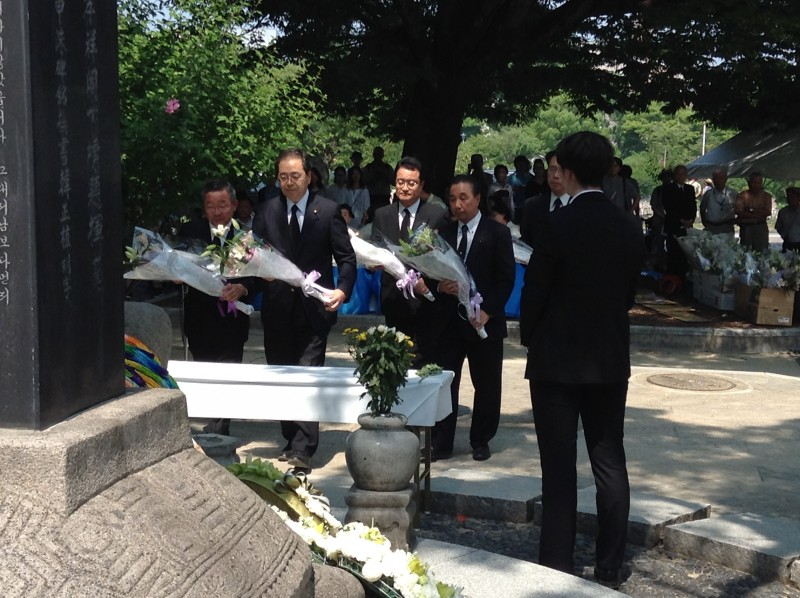 慰霊碑に献花する さいとう鉄夫(左から2人目)